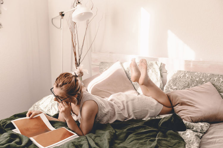 Woman reading book while lying on bed at home