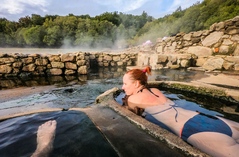 Woman wearing bikini while lying in hot spring