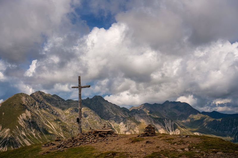 Wooden cross on mountain against sky