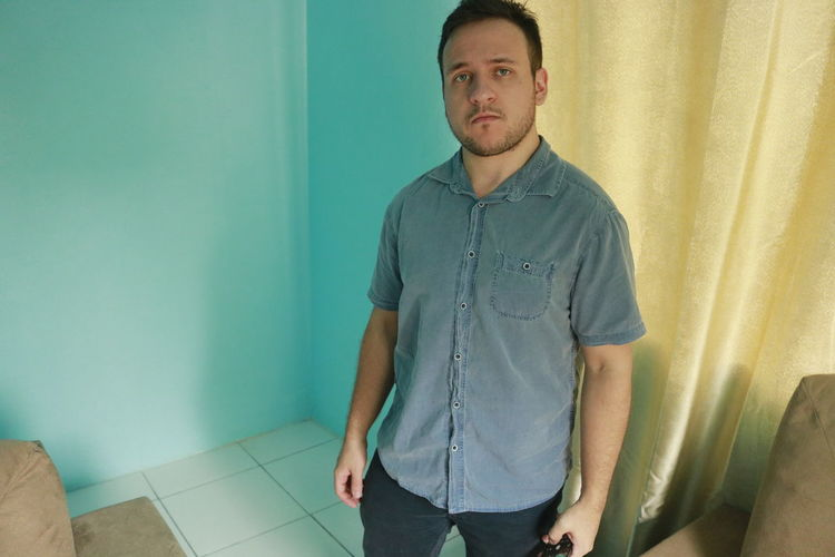Blue Eyes Looking At Camera Standing Indoors  One Person Young Adult Front View Casual Clothing Three Quarter Length Portrait Young Men Real People Wall - Building Feature Home Interior Lifestyles Leisure Activity Blue Hands In Pockets Men Jeans Turquoise Colored