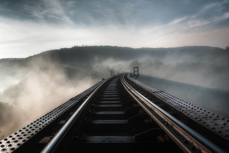 Railroad tracks in foggy weather against sky