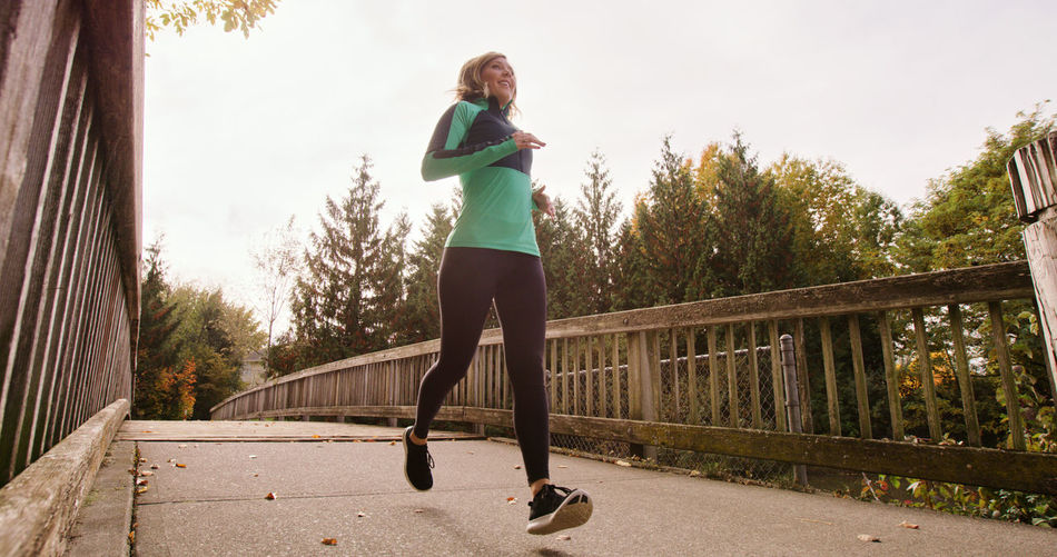 Activity Balance Bridge - Man Made Structure Day Exercising Full Length Healthy Lifestyle Jogging Leisure Activity Lifestyles Mature Adult Mature Women Motion One Person One Woman Only Only Women Outdoors Real People Running Sport Sports Clothing Sunlight Tree Vitality Women