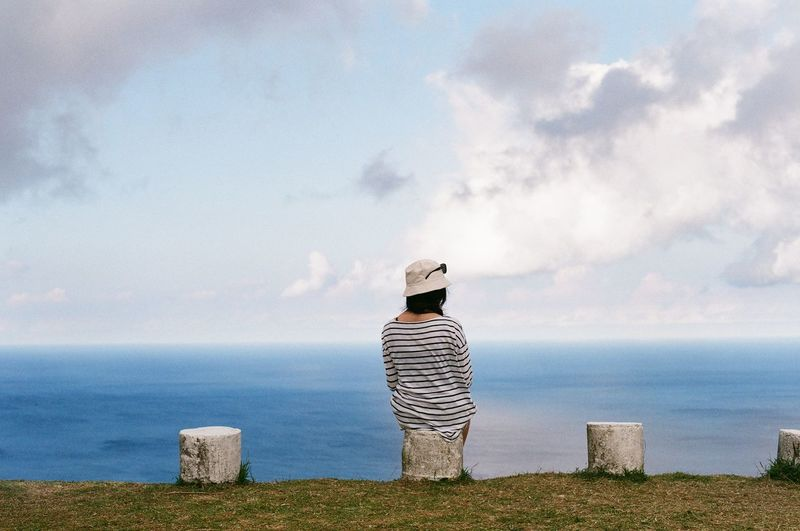 Rear View Of Woman Sitting On Post Against Sea