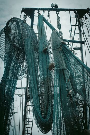 Low angle view of fishing nets hanging against sky