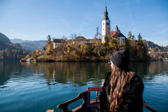 Reaching the church by boat Bled Bled Castle Bled Lake Slovenia Architecture Beauty In Nature Bled, Slovenia Built Structure Day Lake Leisure Activity Lifestyles Nature Nautical Vessel One Person Outdoors People Place Of Worship Real People Rear View Religion Sitting Sky Tree Water Women