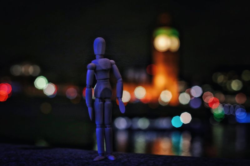 Miniature on retaining wall against illuminated big ben at night