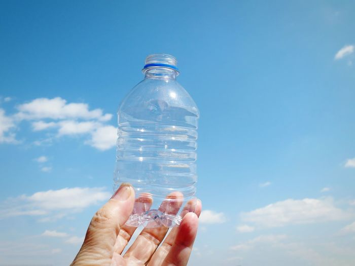 Close-up of hand holding plastic bottle against sky