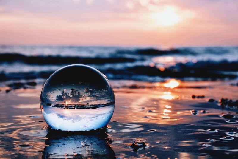 Close-up of crystal ball on beach against sunset sky