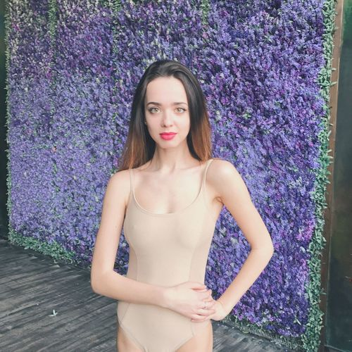 Portrait of woman in one piece swimsuit standing against wall