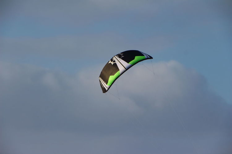 Low angle view of paraglide in cloudy sky