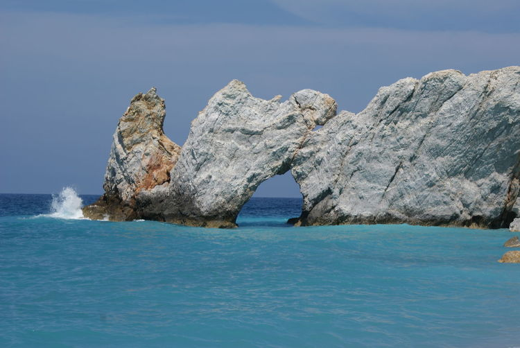 Natural arch on sea against sky