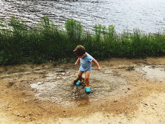 Full Length Of Boy Standing In Puddle By Lake