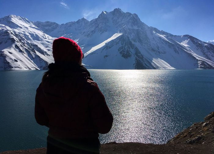 Rear view of woman with lake in background against snowcapped mountains
