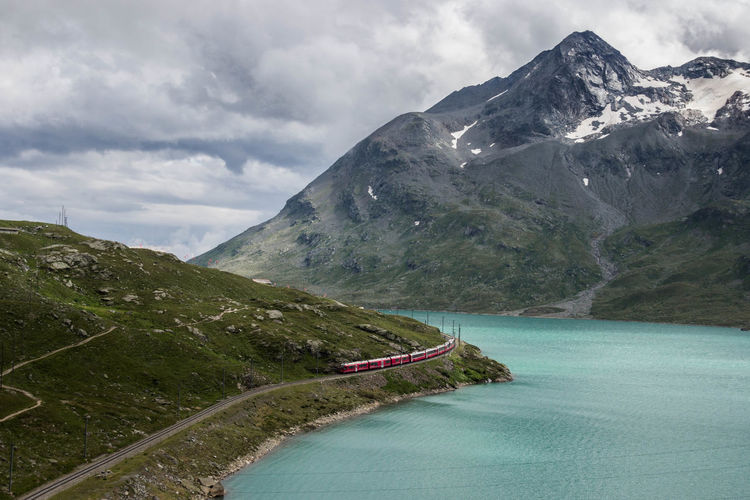 Aerial view of train on railroad track by lake against mountain range