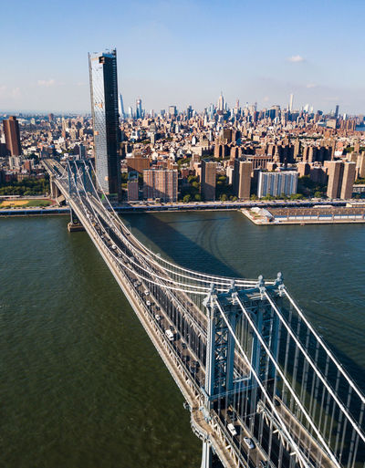 High angle view of manhattan bridge over river by buildings against sky