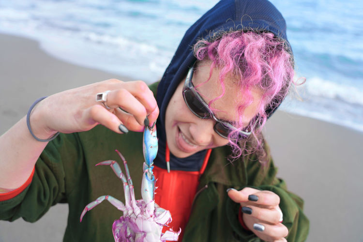 Smiling woman with dyed hair holding dead crab at beach