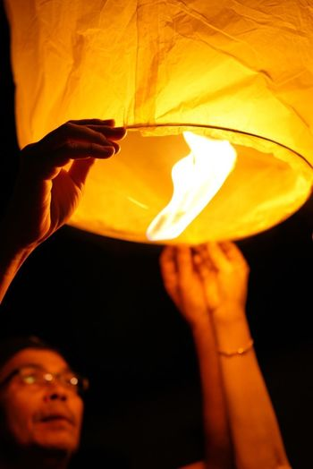 Letting go tanglung Human Hand Heat - Temperature Human Body Part Flame Holding Yellow Lifestyles Burning Lighting Equipment Close-up Igniting Real People One Person Illuminated Women Paper Lantern Indoors  Night Oil Lamp People EyeEmBestPics Chinese New Year Chinese Lantern Festival Chinese Culture