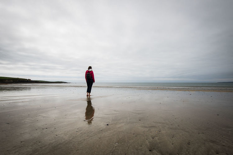 Rear view of woman standing on beach against sky