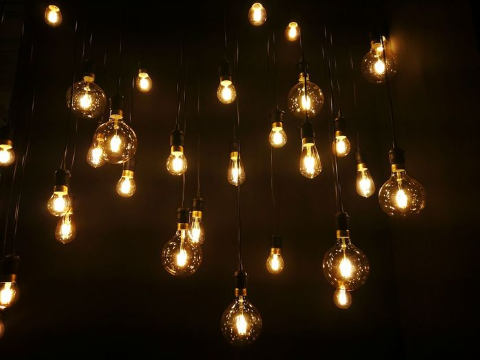 Low angle view of electric bulbs hanging in darkroom