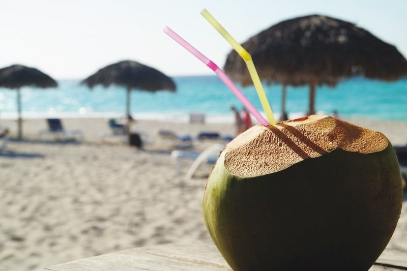 Close-up of coconut and straws on beach
