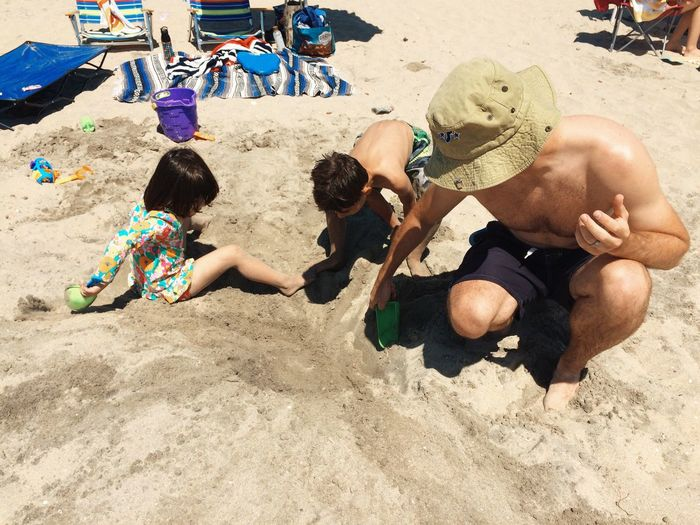 High Angle View Of Father And Kids Digging Sand At Beach On Sunny Day