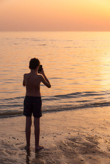 Rear view of shirtless boy photographing while standing at beach against clear sky during sunset
