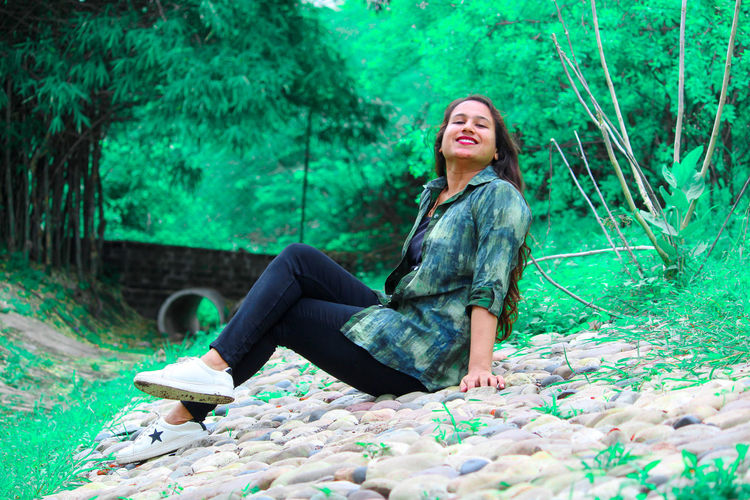 Portrait of young woman smiling while sitting against trees at park