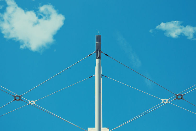 Low angle view of cables connected on pole against blue sky
