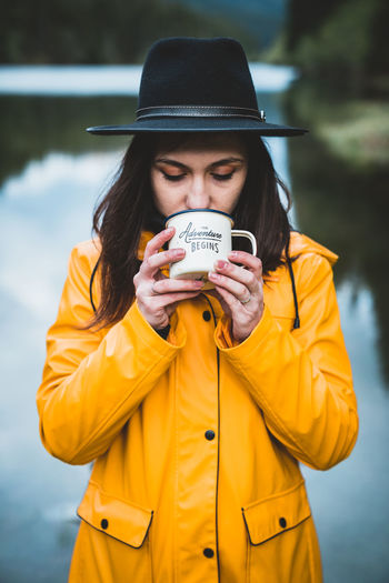 Young woman drinking coffee while standing against lake