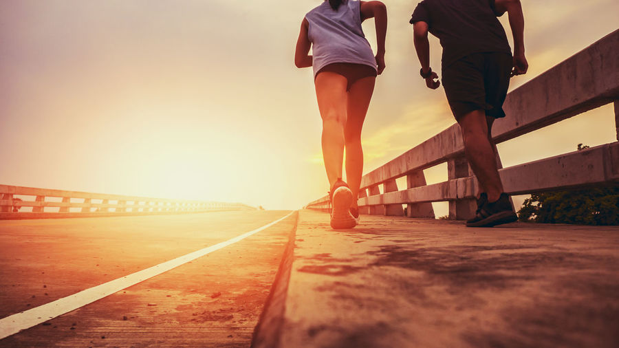 Two runners ran outside. And running on jogging roads. The concept of creating good health Sunset Lifestyles Sky Real People Low Section Men Women Leisure Activity Nature Human Leg People Walking Adult Transportation Two People Architecture Human Body Part Sunlight Rear View Bridge Outdoors Surface Level Couple - Relationship