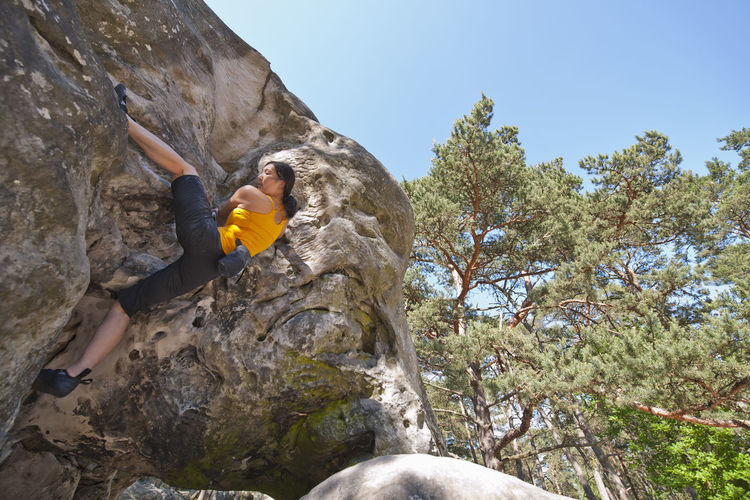 Low angle view of person on rock against mountain