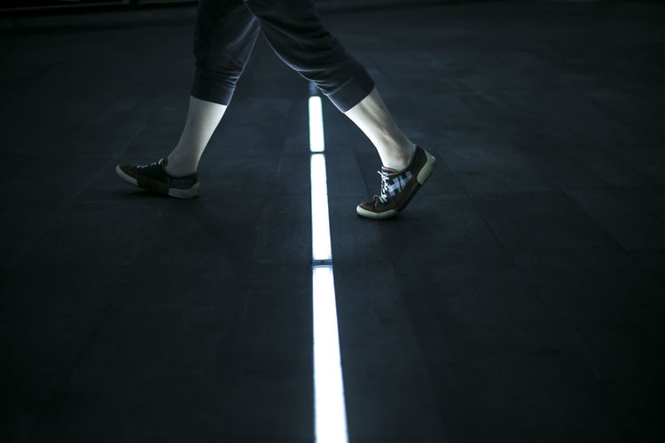 Low Section Of Woman Walking On Illuminated Footpath