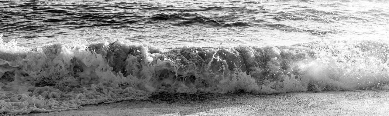 Panoramic view of sea waves splashing on shore