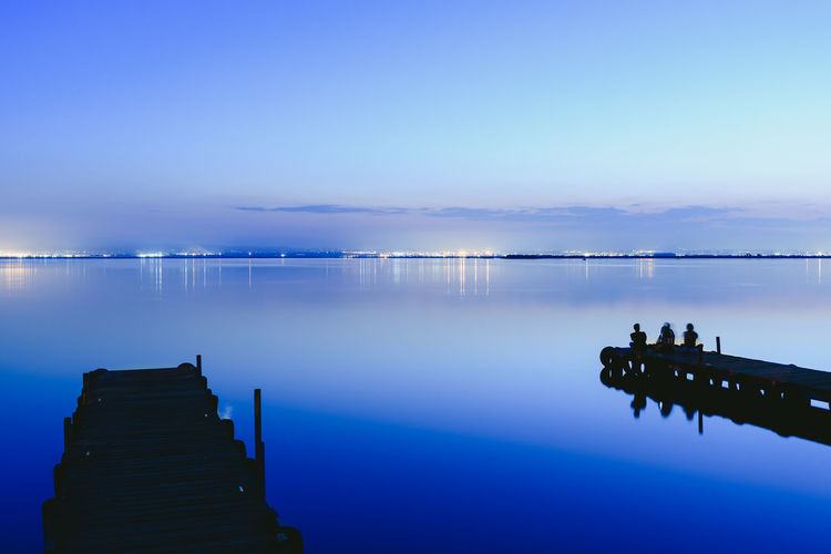 Pier over lake against blue sky at dusk