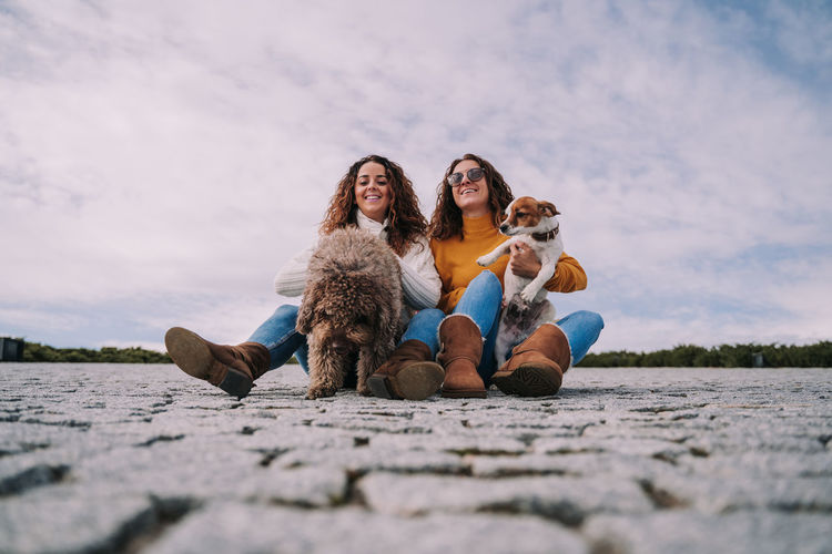 Low angle view of women holding dogs while sitting on land against sky