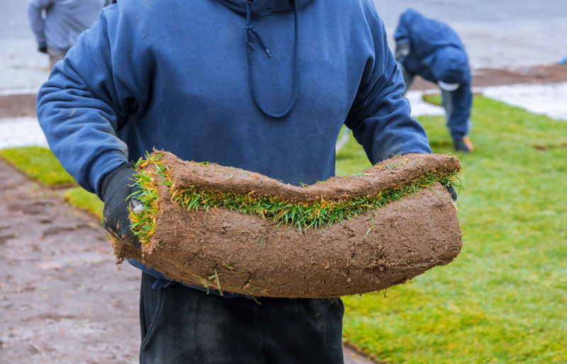 Midsection of man holding turf outdoors