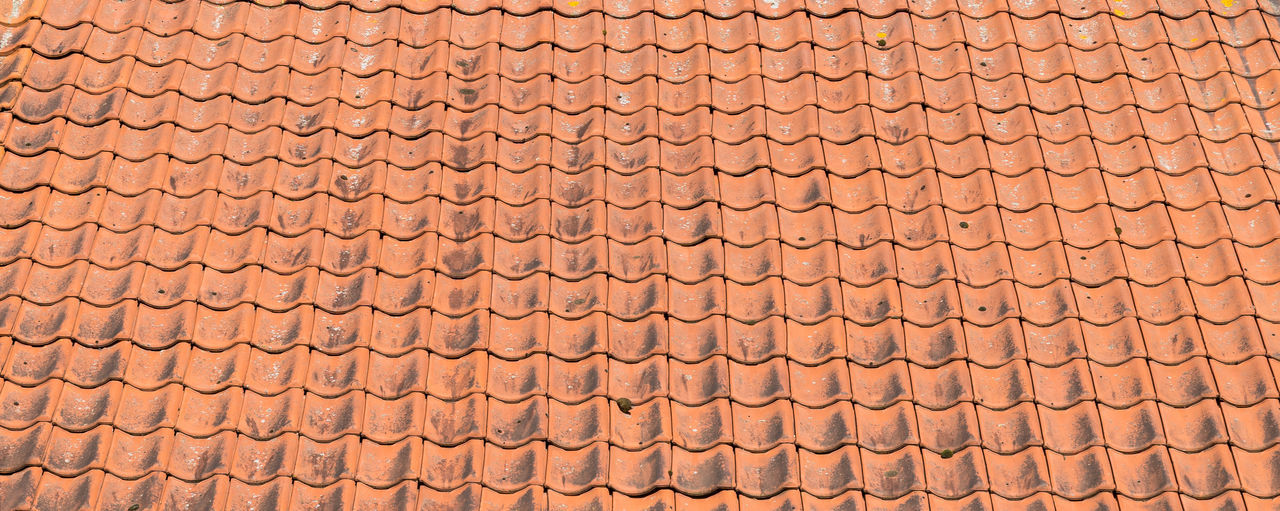 Red roof tiles close up and full frame in rows