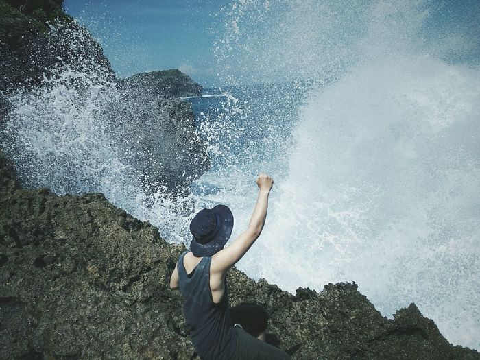 High angle view of man cheering on rock by sea