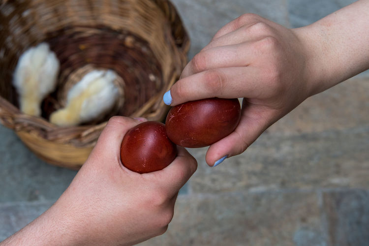 Close-up of hand holding strawberries in basket
