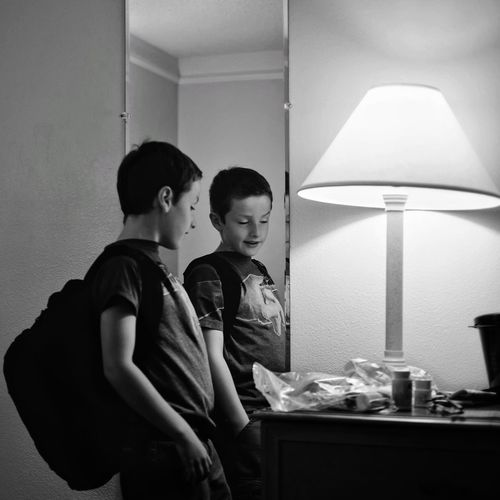 Side view of boy standing by mirror and electric lamp at home