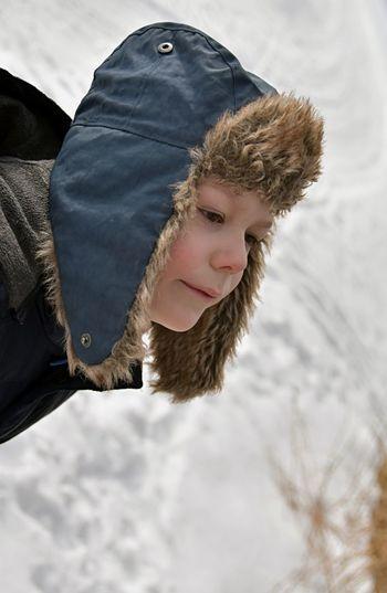 Close-Up Of Boy Wearing Fur Hat At Snow Mountain