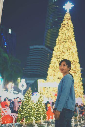 Woman standing on illuminated christmas tree