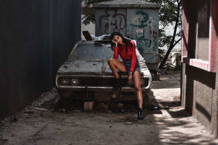 Full Length Of Woman Sitting On Abandoned Car