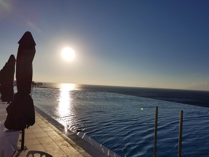 Scenic view of infinity pool by sea against sky during sunset