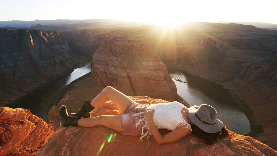 High Angle View Of Woman Lying On Rock Formation Against Horseshoe Bend