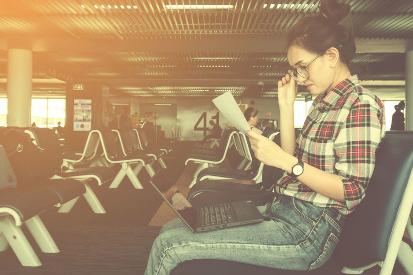 young female using laptop and business chart while while waiting for her flight at airport terminal ;business travellers waiting for their flight at airport Check-in Holiday International Plane Sitting Station Transport Transportation Waiting Airline Airport Arrival Chart Communication Flight Inside Internet Journey Laptop Lounge People Professional Technology Vacation Website