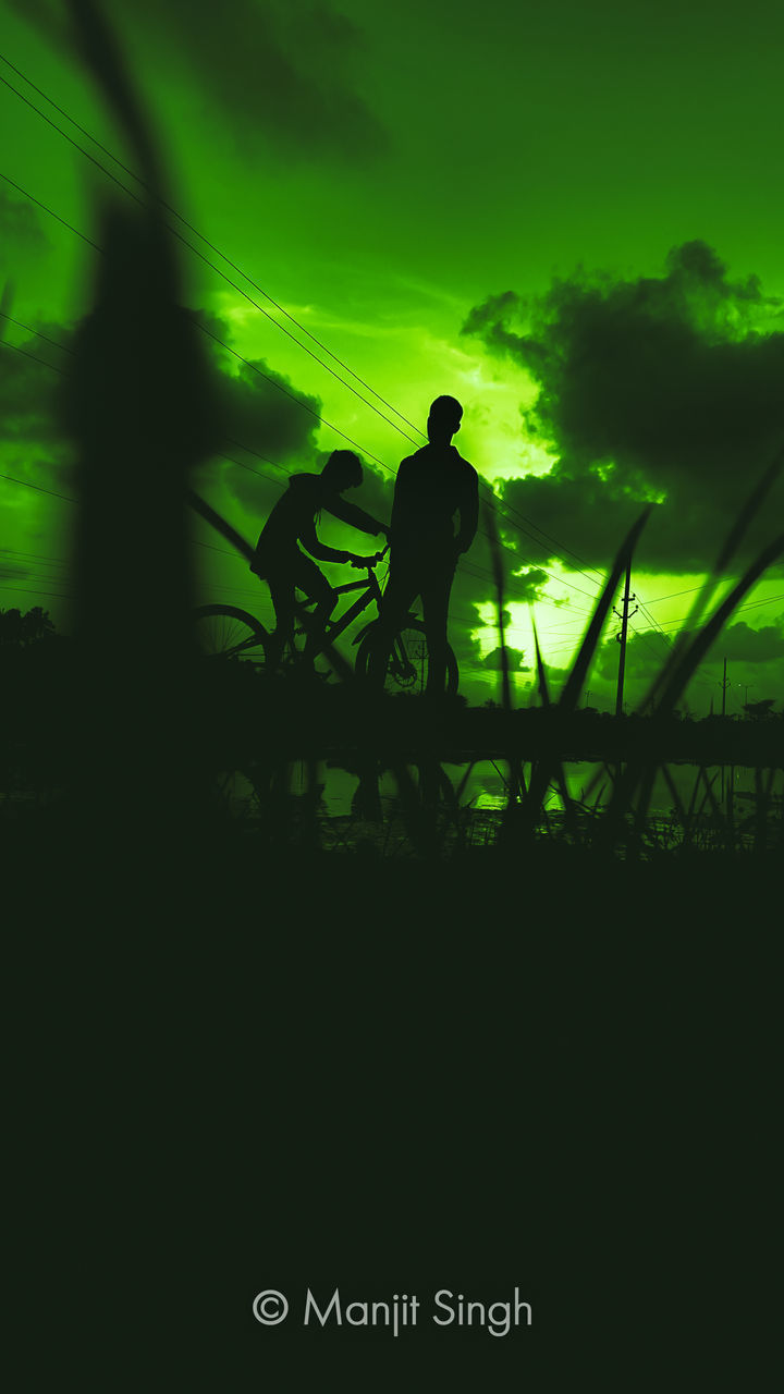 REAR VIEW OF SILHOUETTE MAN AND BICYCLE AGAINST SKY