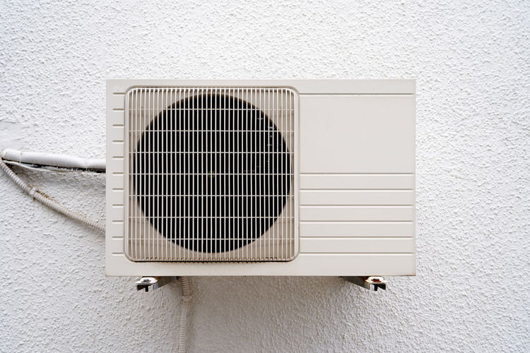 Close-up of electric fan on white wall