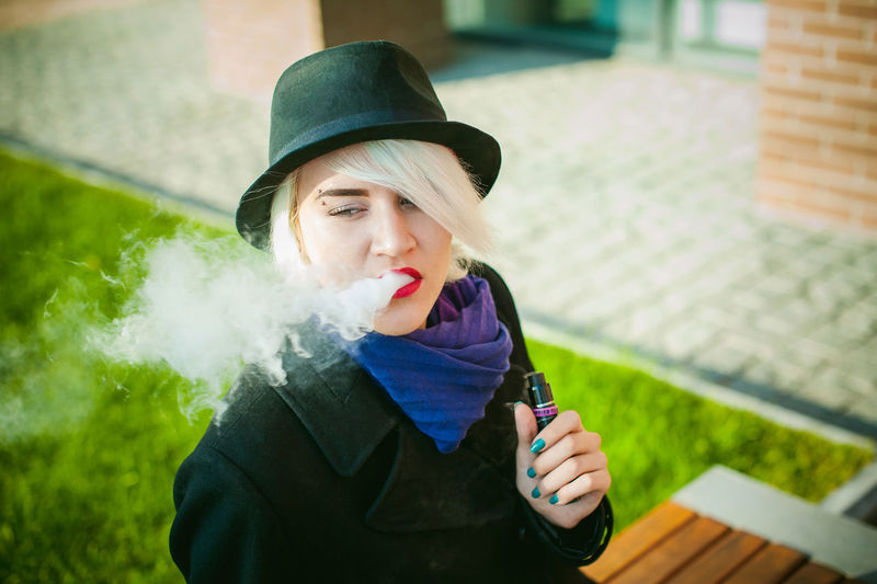 Young Woman Smoking While Standing By Built Structure