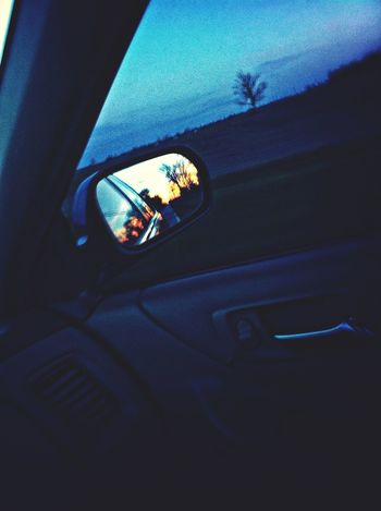 Watching The Sunset On The Road Through The Mirror